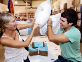 Couple play fighting with pillows