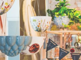 Grey ceramic jelly mould hanging planter in the foreground with botanical print ceramic hanging ...