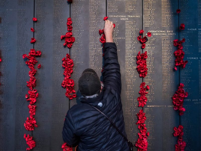 man places poppy on Roll of Honour
