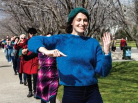 Young Caucasian woman wearing a green beanie and blue sweater dancing