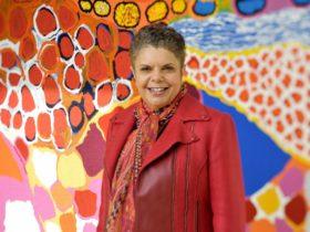 Deborah Cheetham in front of Dulka Warngiid tapestry