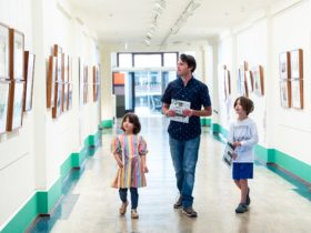 Man and two children walk down a wide bright exhibition hallway looking at framed political cartoons