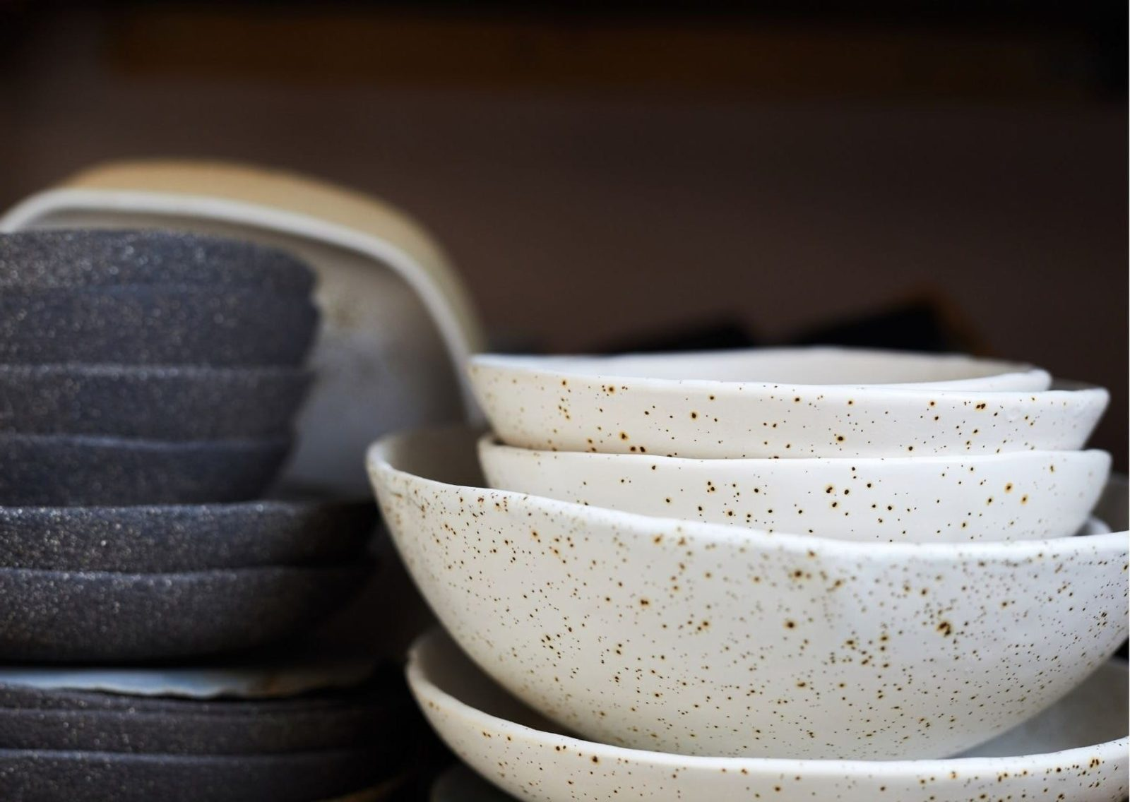 Two stacks of pottery bowls. Black bowls on the left and white bowls with specks on the right