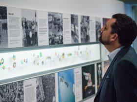 Man looking at exhibition images, text and displayed badges