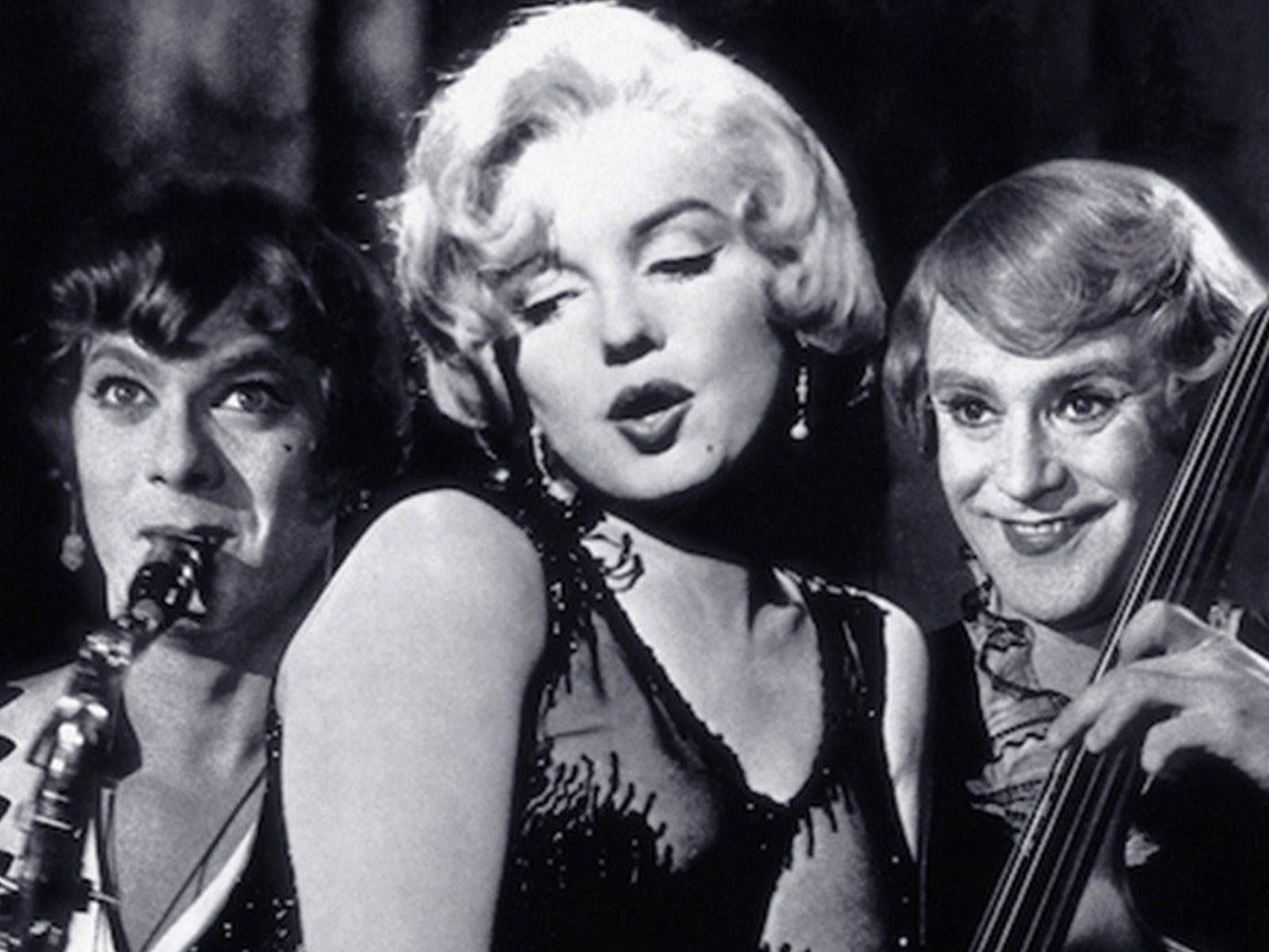 A woman and two men in drag playing instruments