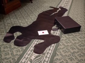 Silhouette cut-out of a body on green carpet next to briefcase and envelope