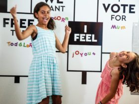 Two girls laughing at interactive letter wall in MoAD's PlayUP exhibition space
