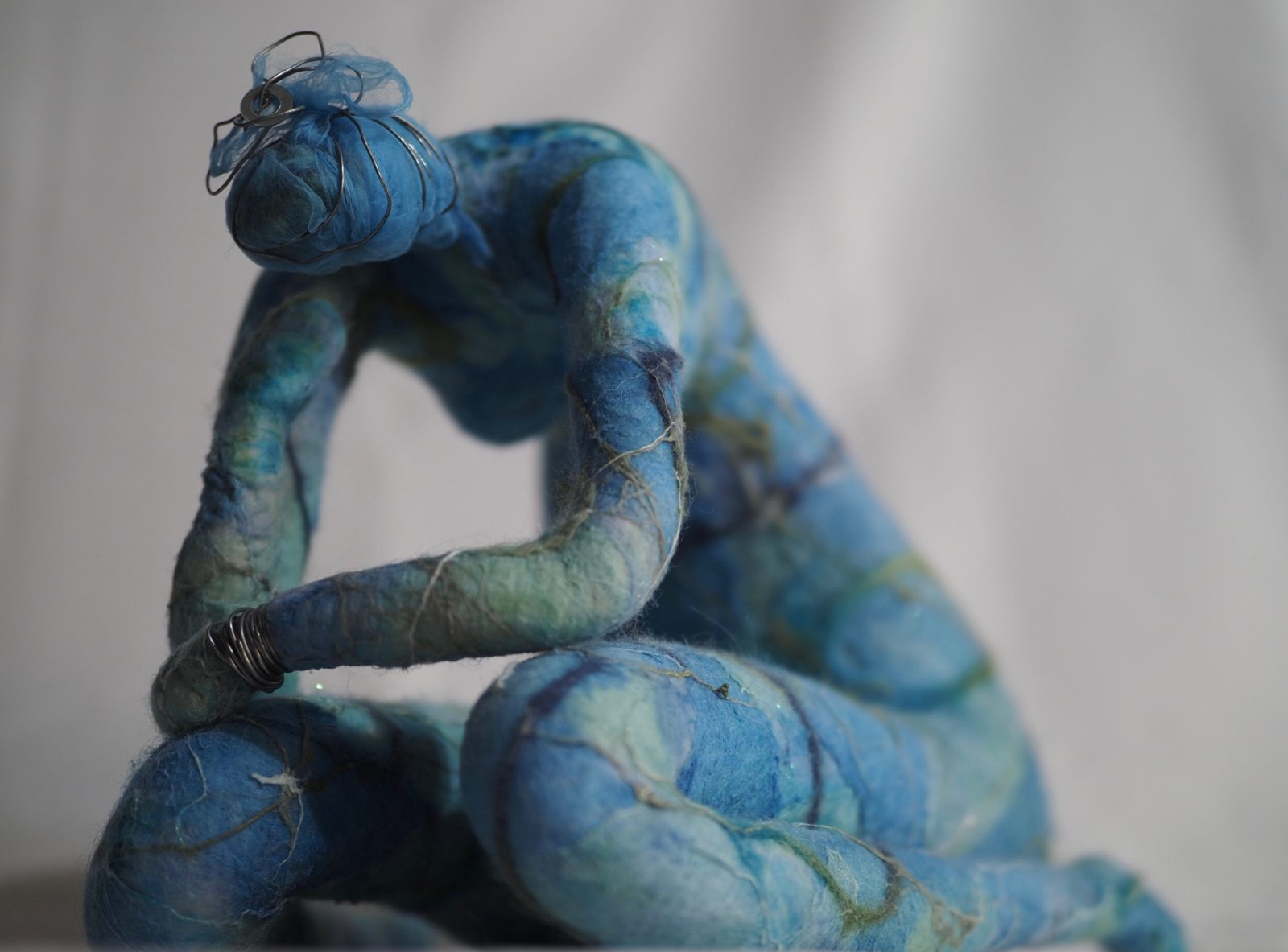 Hand-felted sculpture of a kneeling woman. Materials include wool, silk and wire. Approx 20cm high.