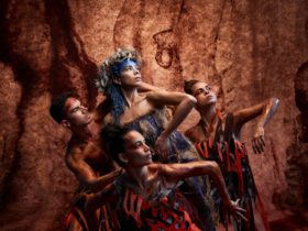 Four Bangarra Dance Theatre dancers pose in front of a painted rock face