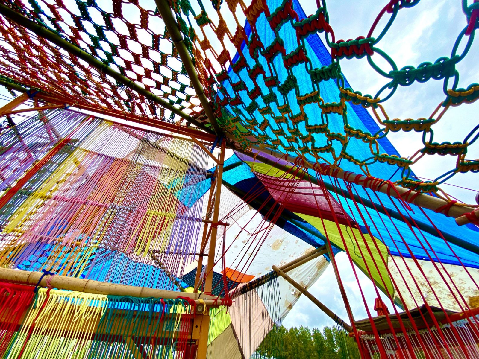 Colourful string netting is woven around bamboo poles creating a colourful tent