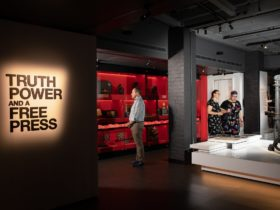 MoAD's Truth Power and a Free Press exhibition entry with three visitors looking at displays