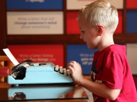 Young boy in red shirt typing at light blue typewriter in MoAD's Yours Faithfully exhibition space