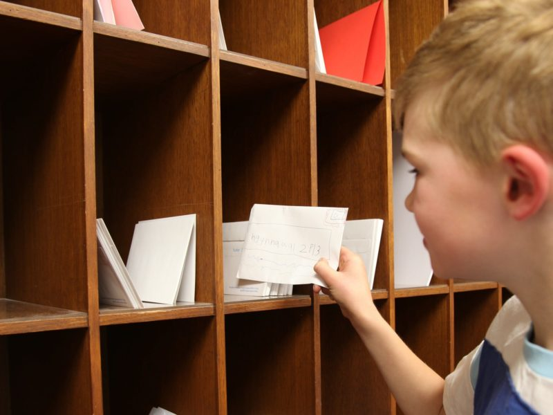 Boy placing envelope into a wooden pigeon hole at Old Parliament House