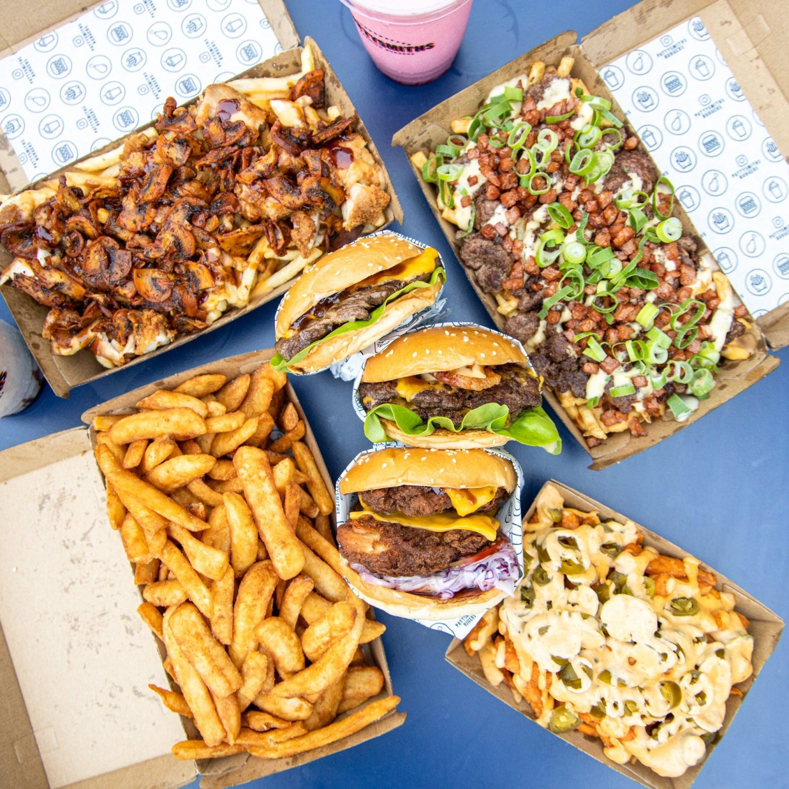 Burgers, fries and drink on a table