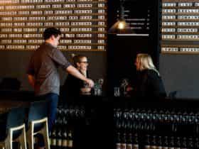 Two women enjoy glasses of wine indoors