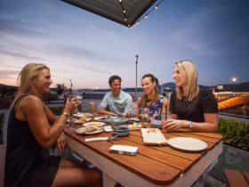 People eating outdoors with views of the lake