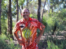 Photo showing Larry Brandy, wearing an Aboriginal shirt, smiling and looking at the camera