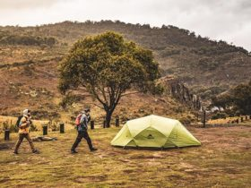 Two men walk past a green tent at Blue Waterholes campground, Kosciuszko National Park. Photo: