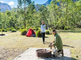 Campers use fire ring facilities at Kedumba River crossing campground, Blue Mountains National Park.