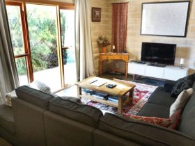 The lounge room is spacious and comfortably seats all six guests. The room looks out over our garden