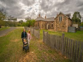 Family with baby walking past Post Office Residence in Hill End Historic Site. Photo: John Spencer/O