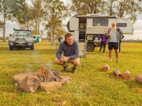 Man sitting around fire with caravan in background
