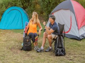 2 campers sitting with their backpacks with their tents set up in the background. Photo: John Spence