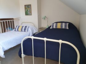 Two single beds beautifully made with blue covers and pillows in a upstairs bedroom.