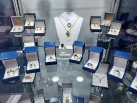 Sapphire Jewellery displayed on glass shelf in cabinet.