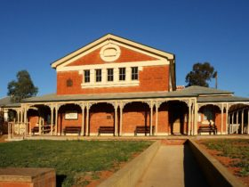Two storey redbrick building with arched verandah