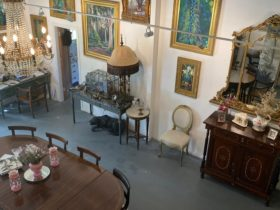 Gallery room. Paintings of peacocks and landscapes are on the wall, above a table, chairs and lamp.