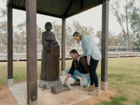Couple viewing redgum statue
