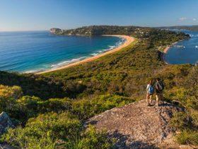 Two people walking to Barrenjoey Lighthouse, admiring coastal views over Ku-ring-gai Chase National
