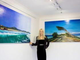 Artist in gallery beside oil paintings
