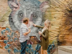 A man and woman touch a mural of a possum on a brick wall in Memorial Plaza, Corowa.