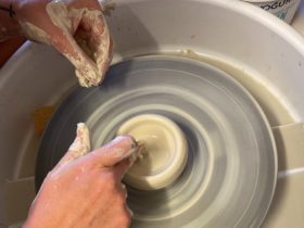 picture shows hands touching clay on a pottery wheel