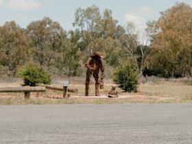 A scrap metal swagman and dog, set in a rural Australian landscape.