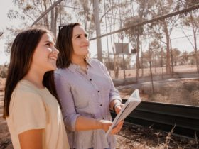 Mother and daughter smiling looking at huge bird aviary