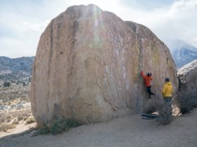 A boulderer climbing a free standing boulder in the buttermilks with a spotter