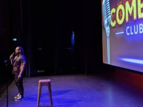 Comedian standing in front of a stool with a screen saying Casula Comedy Club at the back