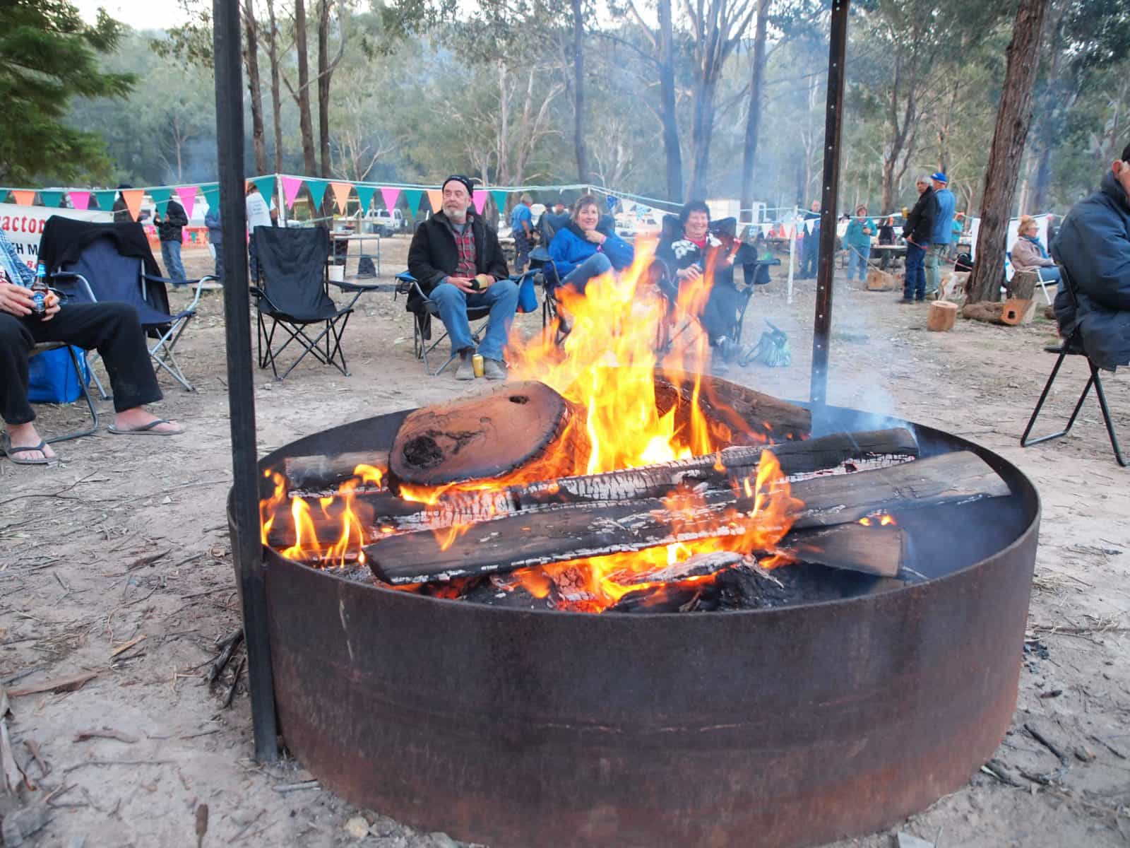 Sitting around a large campfire pit at the Clarence Valley Camp Oven Festival