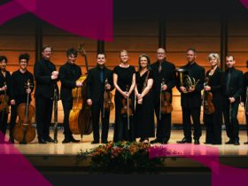 Musicians of the Australian Romantic & Classical Orchestra lined up on stage, holding instruments.