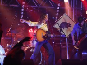 Woman lunging on stage, guitar in hand, one arm outstretched, singing. Wombat ahead sign background