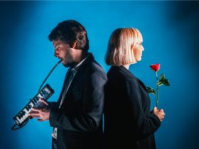 man and woman facing away from each other, woman holding a rose, man holding a mini piano,