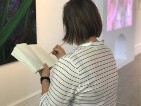 A person draws a a line ruled journal in front of a colourful plant artwork