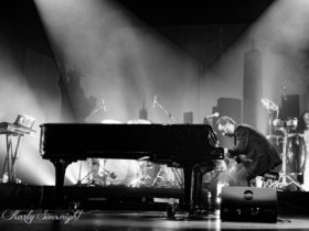 Man playing piano on stage, black and white photo