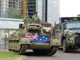 Museum's Matilda Tank named ACE drives past a contemporary Regimental Bushmaster in Lancer Barracks