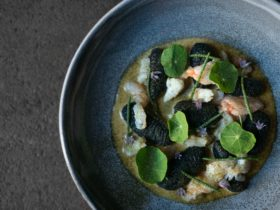 A dish of hand rolled squid ink gnocchi, crab, lobster bisque and garden nasturtiums