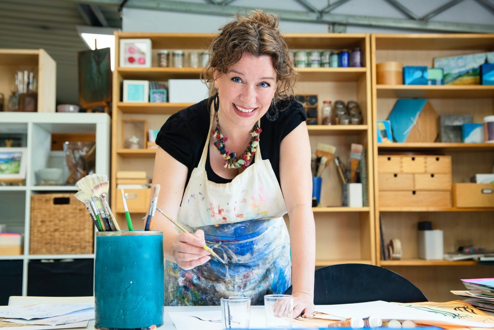 Vivianne painting in studio with bookcases behind her and a jug of brushes on the table