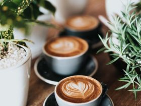 three cups of flat white coffee with heart coffee art